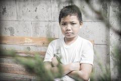 Junger asiatischer Junge, der allein im Park sitzt Lizenzfreie Stockfotografie