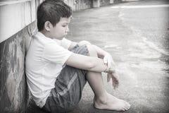 Junger asiatischer Junge, der allein sitzt Stockbilder