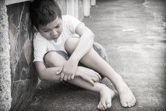 Junger asiatischer Junge, der allein sitzt Stockfotos