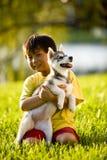 Junger asiatischer Junge, der den Welpen sitzt auf Gras umarmt Stockfoto
