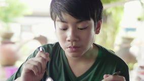 Junger asiatischer Junge, der gebratenen Reis mit Fleisch zum Fr?hst?ck isst stock video