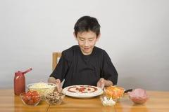 Junger asiatischer Junge, der selbst gemachte Pizza bildet stockfotos