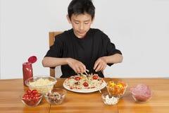 Junger asiatischer Junge, der selbst gemachte Pizza bildet stockfotografie