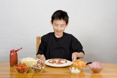 Junger asiatischer Junge, der selbst gemachte Pizza bildet stockfoto