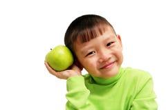 Junger asiatischer Junge mit einem großen grünen Apfel Lizenzfreie Stockfotografie