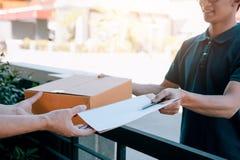 Junger asiatischer lächelnder Mann beim Liefern einer Pappschachtel an das Frauenholdingdokument an unterzeichnende Unterzeichnun stockbilder