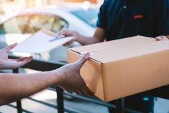 Junger asiatischer l?chelnder Mann beim Liefern einer Pappschachtel an das Frauenholdingdokument an unterzeichnende Unterzeichnun stockfotografie