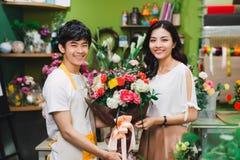 Junger asiatischer männlicher Florist Have Conversation mit seinem Kunden herein stockbilder