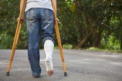Junger asiatischer Mann auf Krücken mit Baumhintergrund Lizenzfreie Stockfotografie