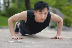 Junger asiatischer Mann, den das Handeln drückt, ups im Freien Stockfoto