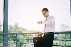 Junger asiatischer Mann, der überprüfend Zeit halten steht und Aktenkoffer wi stockbilder