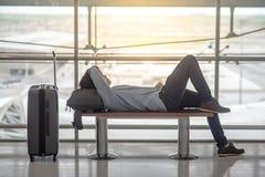Junger asiatischer Mann, der auf Bank im Flughafenabfertigungsgebäude liegt stockbild