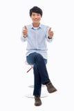 Junger asiatischer Mann, der Daumen zeigt. Stockfotos