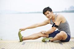 Junger asiatischer Mann, der draußen trainiert Stockbild