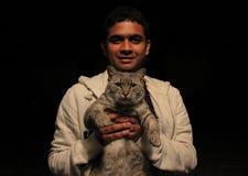 Junger asiatischer Mann, der eine Katze mit der Liebe und Lächeln, die Kamera mit einfachem schwarzem Hintergrund betrachtend häl stockbild