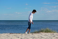 Junger asiatischer Mann, der entlang dem Strand sich entspannt lizenzfreie stockfotografie