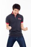 Junger asiatischer Mann, der Faust und glückliches Zeichen zeigt. Stockfoto