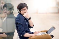 Junger asiatischer Mann, der Gläser oben auf Nase bei der Anwendung des Laptops drückt Stockbilder
