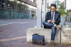 Junger asiatischer Mann, der Handy betrachtet Lizenzfreies Stockfoto