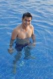 Junger asiatischer Mann, der im klaren Wasserpool und -c$lächeln steht Lizenzfreies Stockfoto