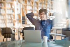 Junger asiatischer Mann, der mit den Händen hinter Kopf in der Bibliothek sitzt lizenzfreie stockfotografie