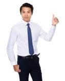 Junger asiatischer Mann, der sich Daumen zeigt Stockfotos