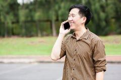 Junger asiatischer Mann, der am Telefon beim Lächeln spricht Stockfotografie