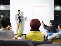 Junger asiatischer Mann, der Unternehmensplan darstellt Lizenzfreies Stockfoto