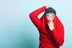 Junger asiatischer Mann, der versucht, von der roten Strickjacke zu nehmen Lizenzfreies Stockfoto