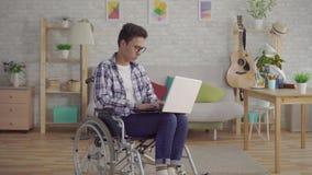 Junger asiatischer Mann des Porträts in den stilvollen Gläsern behindert in einem Rollstuhl mit einem Laptop im Wohnzimmer des Ha stock video footage