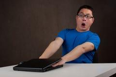 Junger asiatischer Mann erhielt seine Hände gehaftet im Laptop Lizenzfreies Stockbild