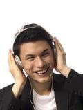 Junger asiatischer Mann mit Kopfhörern Stockfoto