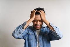 Junger asiatischer Mann setzte Hände zu seinem Kopf Er glaubender Kranker und Kopfschmerzen passend zum Haben einiger Probleme S lizenzfreie stockfotografie