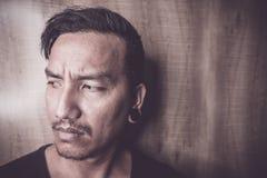 Junger asiatischer Mann sind und allein deprimiert Lizenzfreie Stockfotos