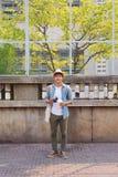 Junger asiatischer Mannreisender und -photograph mit dem Baumwollstoffhemd und -hut, die Fotos machen lizenzfreies stockbild