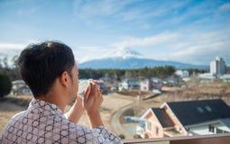 Junger asiatischer Mannstand, der den Fujisan schaut stockfotos