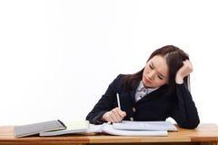 Junger asiatischer Student, der Problem auf Schreibtisch hat. stockbild