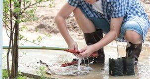 Junger asiatischer thailändischer Junge bereiten schwarzen Boden zum Pflänzchen an im Garten vor stock video footage