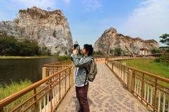Junger asiatischer Tourist, der ein Foto des felsigen Berges des khao Ngu-Stein-Parks, Ratchaburi, Thailand macht lizenzfreie stockfotos