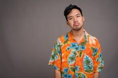 Junger asiatischer touristischer Mann bereit zu den Ferien gegen graues backgrou stockfotos