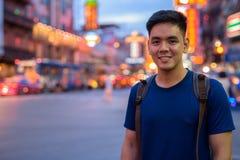 Junger asiatischer touristischer Mann, der bei Chinatown in Bangkok Thailand erforscht stockbilder