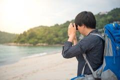 Junger asiatischer Wanderer, der Fotos auf dem Strand macht Stockbilder