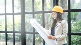 Junger asiatischer weiblicher Bauingenieur in einem gelben harten Schutzhelmhut, der Architekten hält, entwirft in der Hand stock footage
