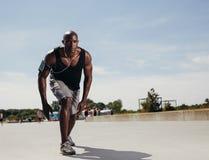 Junger Athlet auf seinem Kennzeichen, zum eines Laufs zu beginnen Stockbild