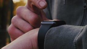 Junger Athlet benutzt intelligente Uhr mit seinem Finger stock footage