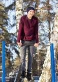 Junger Athlet, der Übung auf horizontaler Stange tut Stockbild