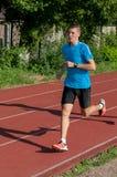 Junger Athlet, der auf Bahn läuft Lizenzfreie Stockfotos