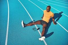 Junger Athlet, der auf Laufbahnwegen vor der Ausbildung sich entspannt lizenzfreie stockfotografie