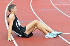 Junger Athlet, der aus den Grund nach laufendem Rennen sitzt Lizenzfreies Stockbild