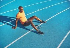 Junger Athlet, der eine Pause vor einem Lauf machend sich entspannt stockbilder